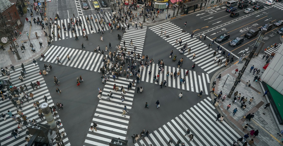 Birds eye view of a 6 way pedestrian crossing in Japan. There are lots of people walking in all sorts of confused directions.